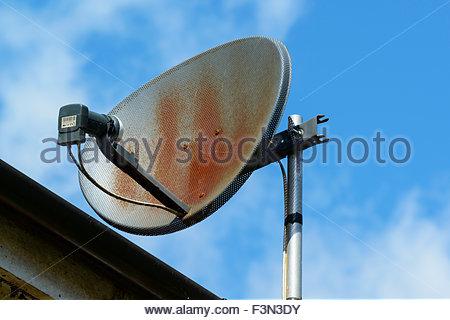 Rusting satellite dish on house, Blandford Forum, Dorset, England UK - Stock Photo