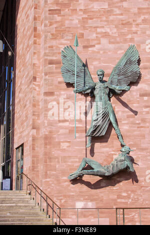 Bronze statue of St Michael conquering the Devil by Jacob Epstein, mounted on a wall next to the entrance to Coventry - Stock Photo
