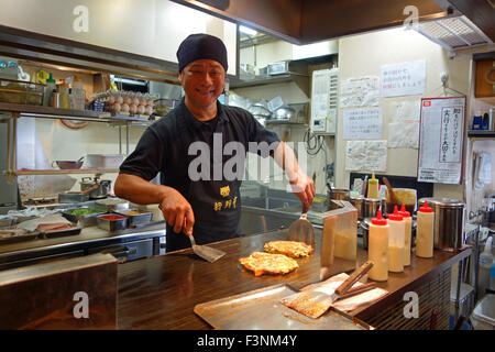 Smiling Japanese chef cooking Okonomiyaki in a restaurant in Osaka, Japan. - Stock Photo