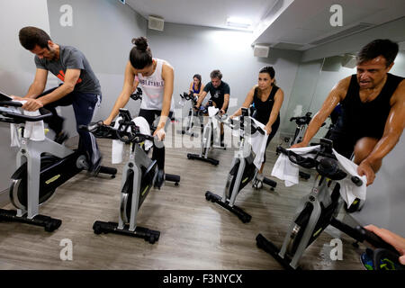 People riding stationary bicycles during a spinning class at the gym - Stock Photo