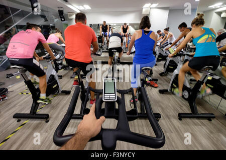 First person perspective of a man riding a stationary bicycle during a spinning class at the gym - Stock Photo