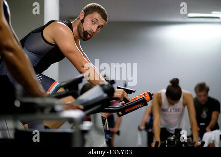 Fitness instructor in front of people riding stationary bicycles during a spinning class at the gym - Stock Photo