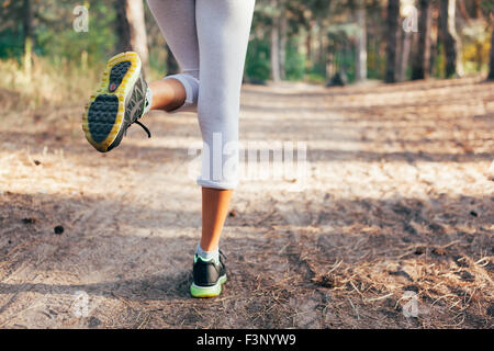 Runner feet running on road close-up on shoe. woman fitness at sunrise - Stock Photo