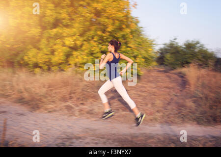 Young woman running on a rural road at sunset in autumn forest. Lifestyle sports background - Stock Photo