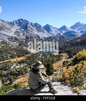 Resting hiker gazes at Little Lakes Valley in Rock Creek Canyon in the Eastern Sierra in Northern California - Stock Photo