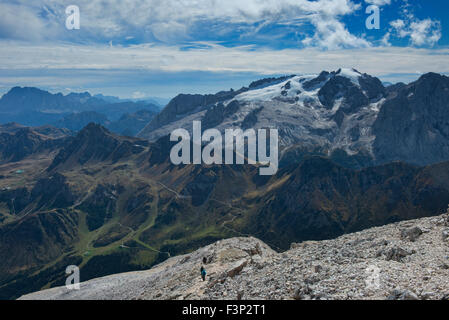 Climbers heading to the summit of Piz Boe with Marmolada (Italy's highest peak) in the background, Dolomites, Italy - Stock Photo