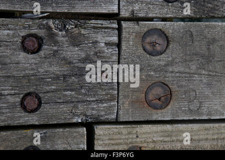 Wooden weathered boards held together with a mixture of metal and wooden fittings - Stock Photo