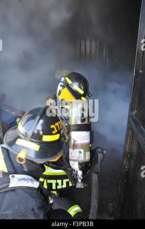 Firefighters with protective equipment in a smoke filled room - Stock Photo