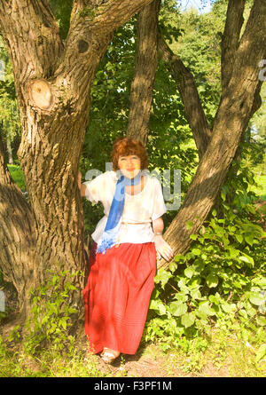 European woman with brown shot hair in white blouse and red skirt in park sitting on big tree. - Stock Photo