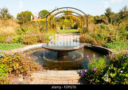 A cottage style garden with a fountain water feature at the Royal Horticultural Society Gardens, Wisley in Surrey. - Stock Photo