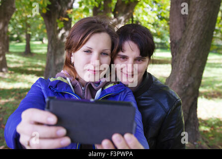 young woman with her mother taking pictures of themselves a mobile phone on autumn day outside - Stock Photo