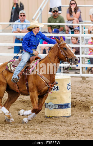 Rodeo Cowgirl On Horseback Competing In Barrel Racing