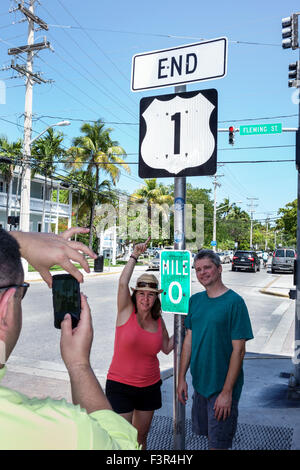 Florida Key West Keys Route 1 Whitehead Street Mile Marker 0 man woman couple posing smartphone picture - Stock Photo