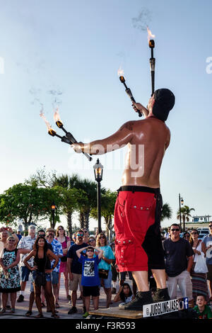 Florida Key West Keys Mallory Square Dock sunset celebration juggler torches flaming fire audience watching - Stock Photo