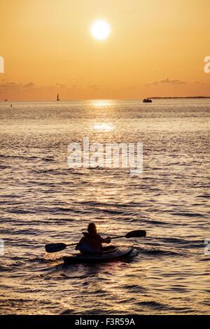 Florida Key West Keys Gulf of Mexico sunset man kayak kayaker kayaking paddling water - Stock Photo