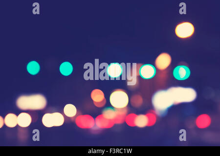 Vintage toned blurred city lights at night, urban abstract background. - Stock Photo