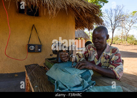 Man with sewing machine in front of a hut, Zambia, Africa - Stock Photo