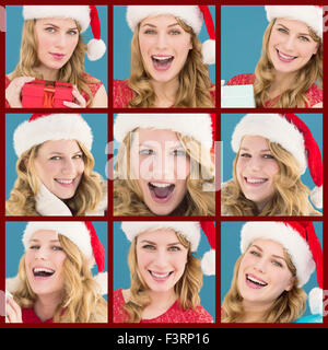Composite image of blonde woman in santa hat standing with gift - Stock Photo