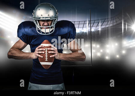 Composite image of angry american football player holding ball - Stock Photo
