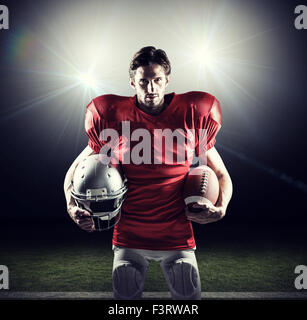 Composite image of american football player in red jersey holding helmet and ball - Stock Photo