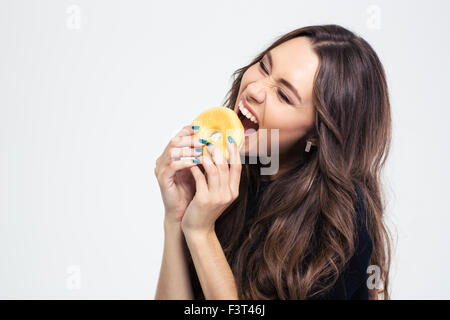 Portrait of a happy woman eating donut isolated on a white background - Stock Photo