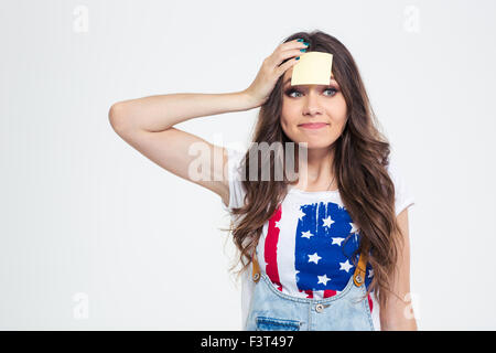 Portrait of a happy woman with sticky note on forehead isolated on a white background - Stock Photo