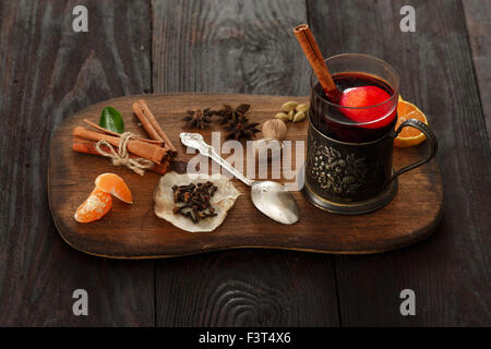 Glass of mulled wine (punch) in glass-holder served on wooden plate with spices over dark wooden table Stock Photo