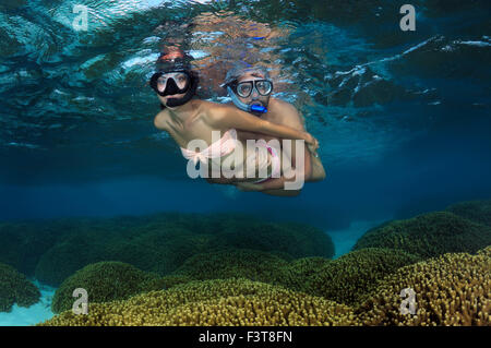Oct. 15, 2014 - Young beautiful woman floats on the surface of the water over the coral reef, Indian Ocean, Maldives - Stock Photo