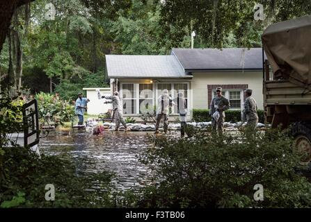 South Carolina National Guard Soldiers unload sandbags to help a resident protect their property from floodwaters - Stock Photo
