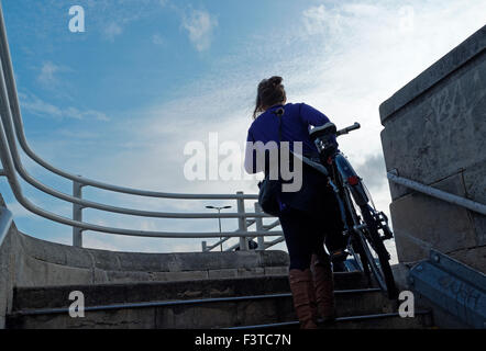 Bicycle commuter climbing stairs with bicycle - Stock Photo