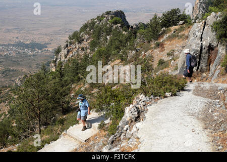 Man and woman on walking tour descending the steps from Buffavento Castle in Besparmak Mountains North Cyprus  KATHY - Stock Photo