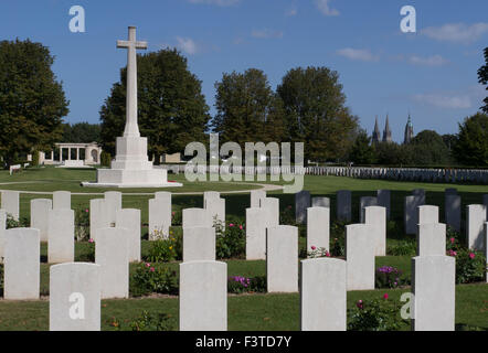 War Graves and Memorial Cross with Bayeux Catherdral in distance - Stock Photo