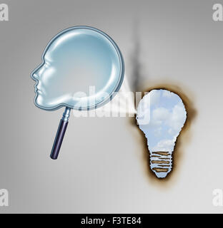 Human creativity concept as a magnifying glass shaped as a head profile creating a hot beam of light burning a hole - Stock Photo