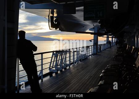 A man looking at the setting sun from the deck of the cruise ship Volendam on the 'Inside Passage' - Stock Photo
