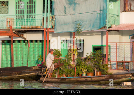 Vietnamese man rowing his timber boat past houses on the mekong river,mekong delta region,south west Vietnam - Stock Photo