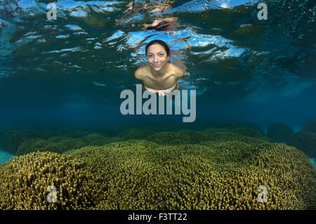 Young beautiful woman floats on the surface of the water over the coral reef, Indian Ocean, Maldives - Stock Photo