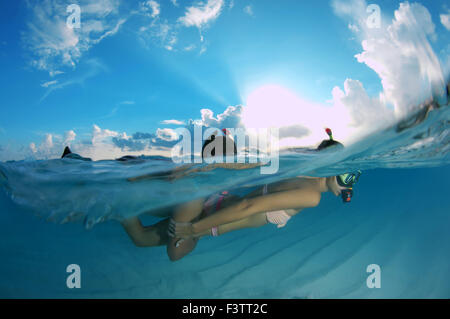Split level, Young beautiful couple floating above a sandy bottom, Indian Ocean, Maldives - Stock Photo