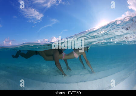 Young beautiful couple floating above a sandy bottom, Indian Ocean, Maldives - Stock Photo