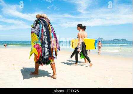RIO DE JANEIRO, BRAZIL - JANUARY 13, 2013: Young Brazilian body boarders pass a vendor selling kanga sarongs on - Stock Photo