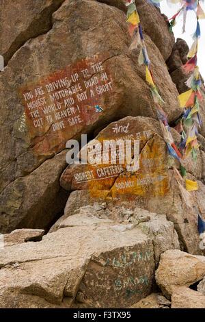 India, Jammu & Kashmir, Ladakh, Leh, Khardung La Pass, road safety notice painted on rock - Stock Photo