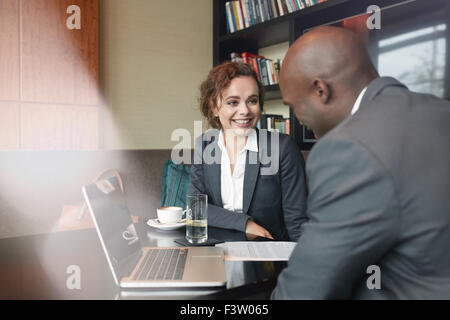 Two business partners sitting in cafe and discussing business plan. Businessman and businesswoman smiling during - Stock Photo