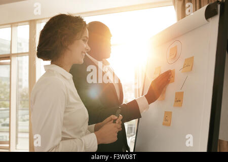Two business colleagues working on project together. Business people putting their ideas on whiteboard during a - Stock Photo