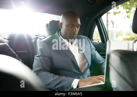 Shot of happy young businessman traveling to work in the luxury car on the back seat and using laptop. African business - Stock Photo
