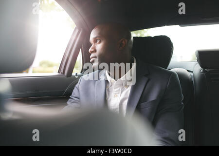 Young african businessman traveling to work in the luxury car on the back seat looking outside the window. - Stock Photo