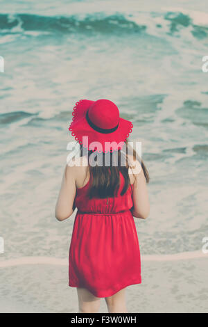 Young woman in a red dress on the beach - Stock Photo