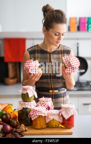 A woman is standing holding jars of vegetables she has just finished preserving. On a wooden cutting board on the - Stock Photo