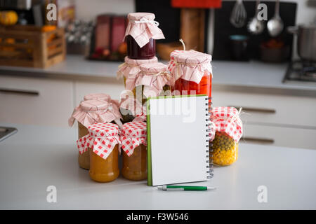 A stack of glass jars filled with preserved vegetables is standing on the kitchen counter. Leaning up against them, - Stock Photo