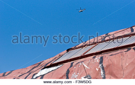 Greek Sheet Metal Roofing Painted Red With Solar Panels And Military Helicopter - Stock Photo