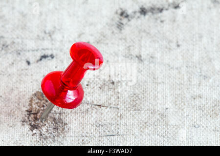 Red pushpin on the old book cover, close-up - Stock Photo