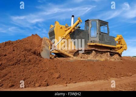 heavy bulldozer moving sand in sandpit - Stock Photo